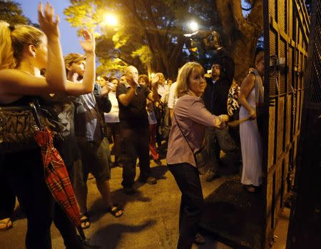 Women smash a police fence during a protest over the death of prosecutor Alberto Nisman, in front of the Olivos presidential residence in Buenos Aires