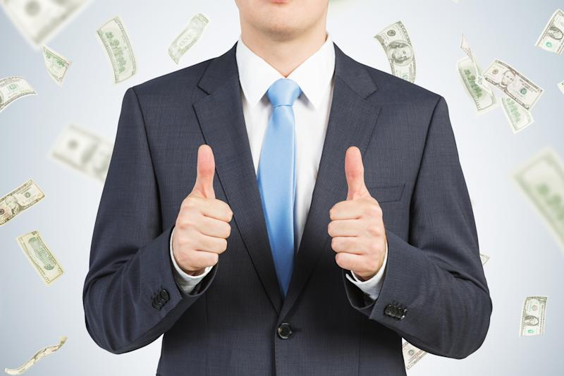 A man in a suit giving two thumbs up