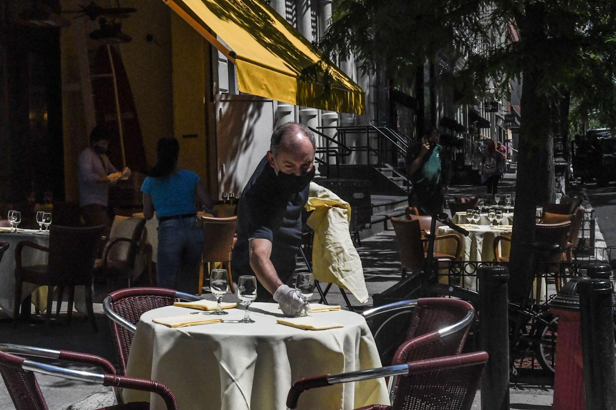 A worker sets an outdoor table for the Cipriani restaurant on June 22, 2020 in the SoHo neighborhood in New York City.