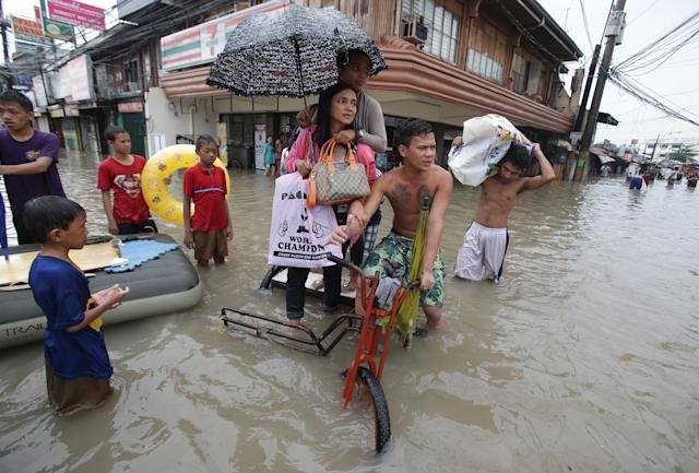 Filipino residents ride a pedicab to cross a flooded street in Las Pinas, south of Manila, Philippines on Monday, Aug. 19, 2013. Torrential rains brought the Philippine capital to a standstill Monday, submerging some areas in waist-deep floodwaters and making streets impassable to vehicles while thousands of people across coastal and mountainous northern regions fled to emergency shelters. (AP Photo/Aaron Favila)