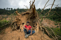 """Elmer Ramirez, 22, sits for a portrait at the site of his home destroyed by a landslide triggered by hurricanes Eta and Iota in the village of La Reina, Honduras, Wednesday, June 23, 2021. """"We made the decision for my wife to go to the United States because she was carrying the [five-month-old] baby and she could stay, but she had to make the whole trip nursing. Hopefully I can meet her in the near future in Miami. Our plan is to be able to build ourselves a house. Nobody leaves thinking of staying in the U.S. because our land is here."""" (AP Photo/Rodrigo Abd)"""