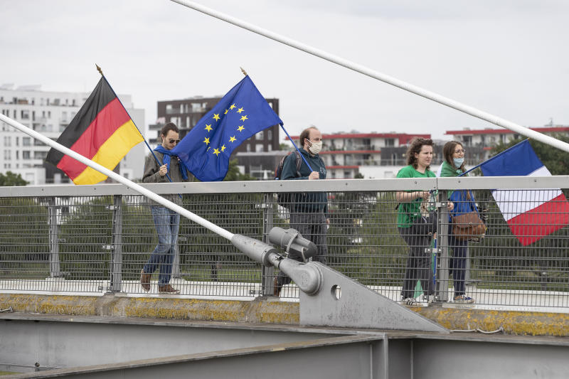 Members of pro-European French and German associations walk on a footbridge over the Rhine river and linking France to Germany, Sunday June 14, 2020 in Strasbourg, eastern France. The majority of European countries will be reopening Monday June 15, 2020 their borders and lifting the restrictions that had been in place during the COVID-19 pandemic. (AP Photo/Jean-Francois Badias)