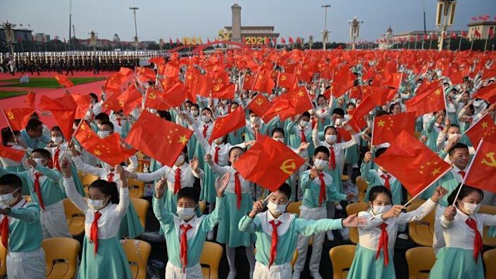 Students wave Chinese flags before the celebration of the 100th anniversary of the founding of the Communist Party of China at Tiananmen Square in Beijing on July 1, 2021.