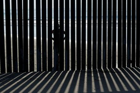 FILE PHOTO: A person looks through the border wall towards the United States at Border Field State Park in San Diego