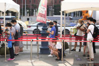 People wait to get coronavirus testing at a makeshift testing site in Seoul, Wednesday, July 28, 2021. South Korea reported a new daily high for coronavirus cases, a day after authorities enforced stringent restrictions in areas outside the capital region. (AP Photo/Ahn Young-joon)