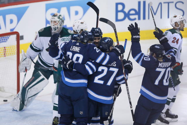 Winnipeg Jets' Paul Stastny (25), Patrik Laine (29), Dustin Byfuglien (33), Nikolaj Ehlers (27) and Joe Morrow (70) celebrate Stastny's goal against Minnesota Wild goaltender Devan Dubnyk (40) during the third period of Game 2 of an NHL hockey first-round playoff series Friday, April 13, 2018, in Winnipeg, Manitoba. (John Woods/The Canadian Press)