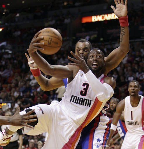 Miami Heat's Dwyane Wade (3) slides past New Jersey Nets' Shelden William scoring two points during the first half of an NBA basketball game in Miami, Tuesday, March 6, 2012. (AP Photo/J Pat Carter)