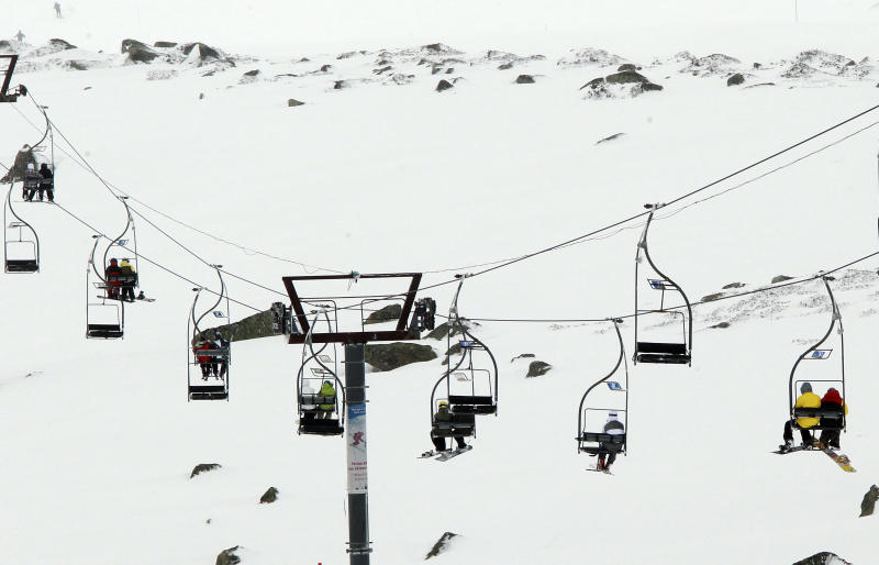 People travel in chairlifts, at the ski resort Porte Puymorens, in southwestern France, Saturday, June 1, 2013. The still-white slopes in the Pyrenees of southern France opened for business on Saturday, turning a cold damp spring into an rare June ski weekend. The Porte-Puymorens ski station opened Saturday morning at 8 a.m. for four hours in fog and light rain _ but plenty of snow with temperatures just above freezing. (AP Photo/Bob Edme)