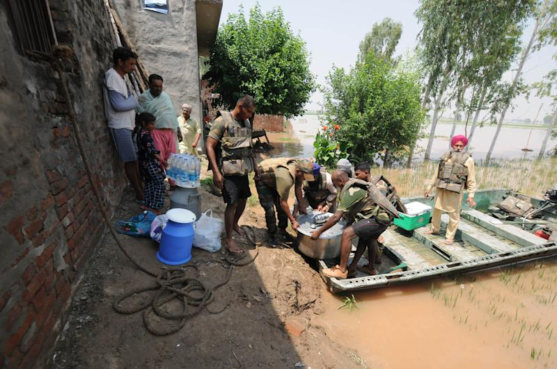 Army personnel carry food for villagers affected by severe floods, at Jamaliwala Village in Ferozpur district. (Photo: Hindustan Times via Getty Images)