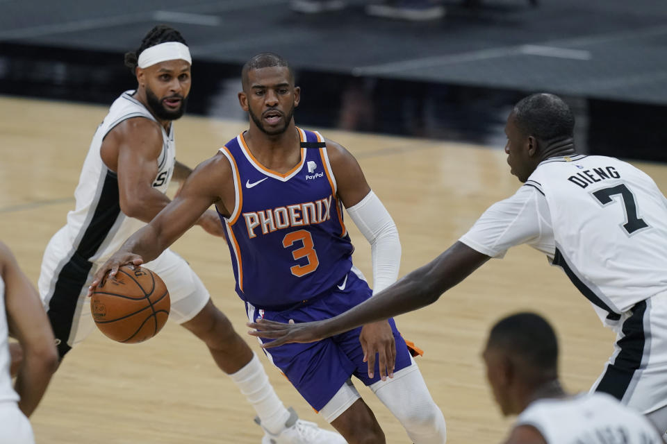 Phoenix Suns guard Chris Paul (3) drives around San Antonio Spurs guard Patty Mills, left, and center Gorgui Dieng (7) during the first half of an NBA basketball game in San Antonio, Saturday, May 15, 2021. (AP Photo/Eric Gay)