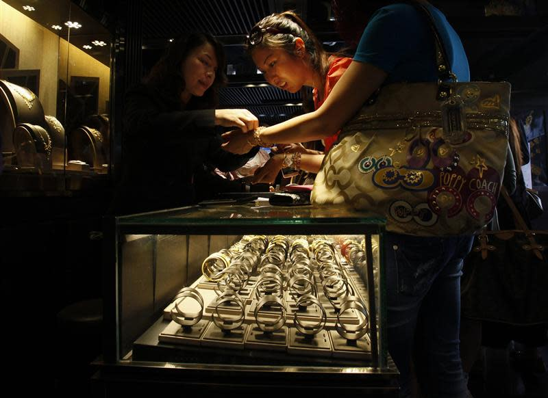 File photo of a mainland Chinese visitor trying on a 24K gold bracelet inside a jewellery store at Hong Kong's Tsim Sha Tsui shopping district