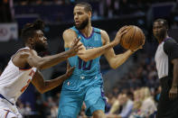Charlotte Hornets forward Caleb Martin, right, keeps the ball from New York Knicks guard Reggie Bullock during the first half of an NBA basketball game in Charlotte, N.C., Wednesday, Feb. 26, 2020. (AP Photo/Nell Redmond)