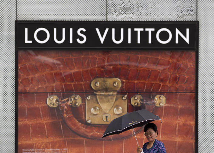 In this July 2, 2012 photo, a Mongolian woman walks past a Louis Vuitton outlet near the Sukhbaatar Square in Ulan Bator, Mongolia. Landlocked with 2.8 million people spread over an area twice the size of Texas, Mongolia is dwarfed by China, with its 1.3 billion people and the world's second largest economy. Fully 90 percent of Mongolia's exports - coal, copper, cashmere and livestock - go to China, which in turn sends machinery, appliances and other consumer goods that account for a third of Mongolian imports. (AP Photo/Andy Wong)