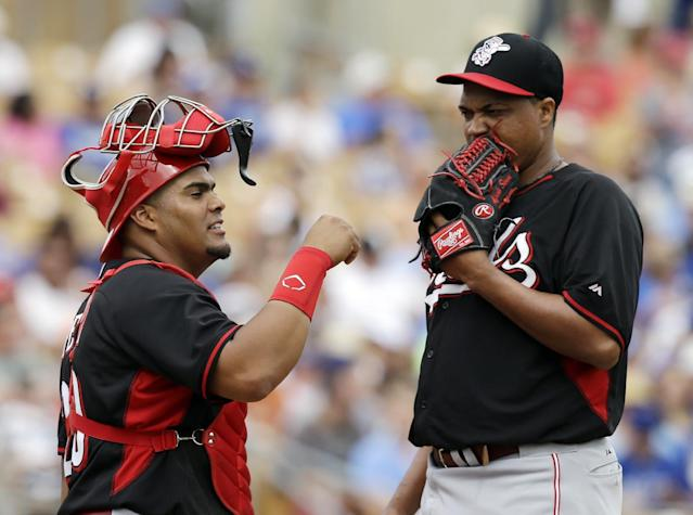 Cincinnati Reds catcher Brayan Pena, left, talks to starting pitcher Alfredo Simon in the third inning of a spring exhibition baseball game against the Los Angeles Dodgers, Thursday, March 13, 2014, in Glendale, Ariz. (AP Photo/Mark Duncan)