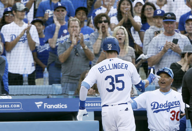 Los Angeles Dodgers' Cody Bellinger gets congratulations from manager Dave Roberts, right, after Bellinger hits a solo home run against the Chicago Cubs during the sixth inning of a baseball game in Los Angeles, Sunday, June 16, 2019. (AP Photo/Alex Gallardo)