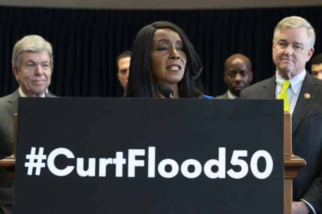 Sen. Roy Blunt, R-Mo., left, and Rep. David Trone, D-Md., right, stand as and Judy Pace Flood, speaks during a news conference to call for the late Curt Flood to be inducted into the Baseball Hall of Fame, on Capitol Hill, Thursday, Feb. 27, 2020 in Washington. (AP Photo/Alex Brandon)