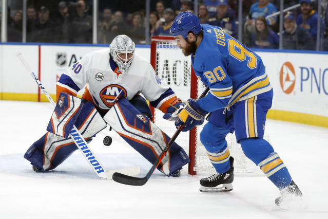 St. Louis Blues' Ryan O'Reilly (90) and New York Islanders goaltender Robin Lehner, of Sweden, watch the puck during the second period of an NHL hockey game Saturday, Jan. 5, 2019, in St. Louis. (AP Photo/Jeff Roberson)