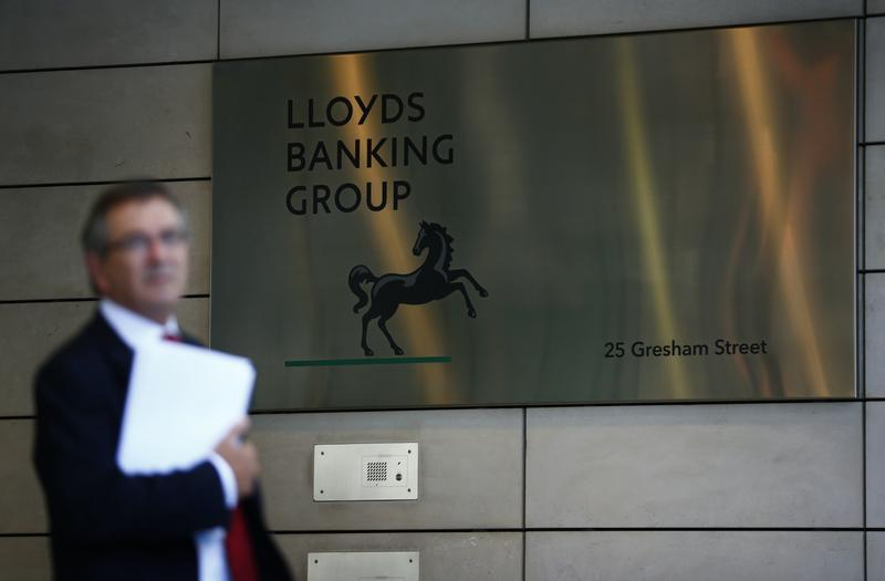 A man waits outside the corporate headquarters of Lloyds Banking Group in the City of London