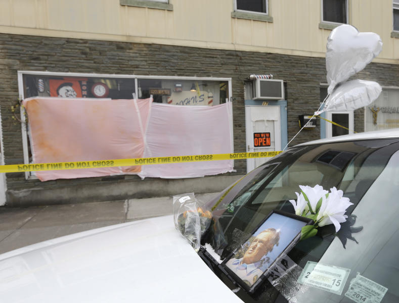 A memorial sits on a vehicle outside John's Barber Shop on, Thursday, March 14, 2013, in Mohawk, N.Y. Two customers were killed at the shop and two others were killed at a car wash in neighboring Herkimer on Wednesday. Authorities say the suspect in the shootings died in a shootout with police SWAT teams Thursday morning. (AP Photo/Mike Groll)