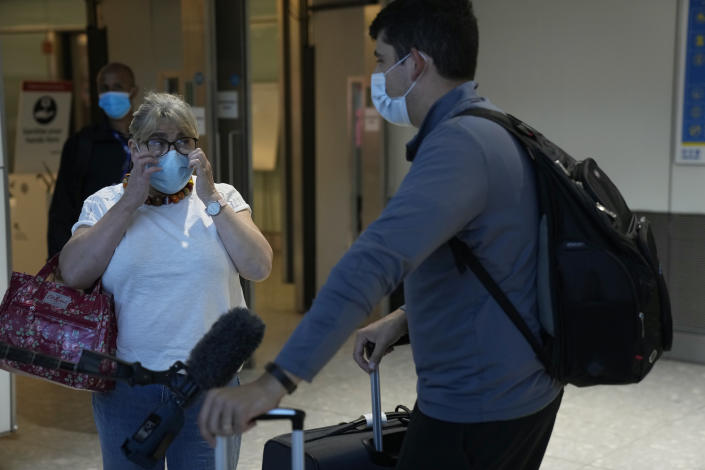 Whilst giving a television interview, Karen Tyler wipes tears of happiness away after greeting her son Jonathan, who she's not seen for over a year and a half, as he arrives on a flight from Houston, Texas, in the U.S., at Terminal 5 of Heathrow Airport in London, Monday, Aug. 2, 2021. Travelers fully vaccinated against coronavirus from the United States and much of Europe were able to enter Britain without quarantining starting today, a move welcomed by Britain's ailing travel industry. (AP Photo/Matt Dunham)