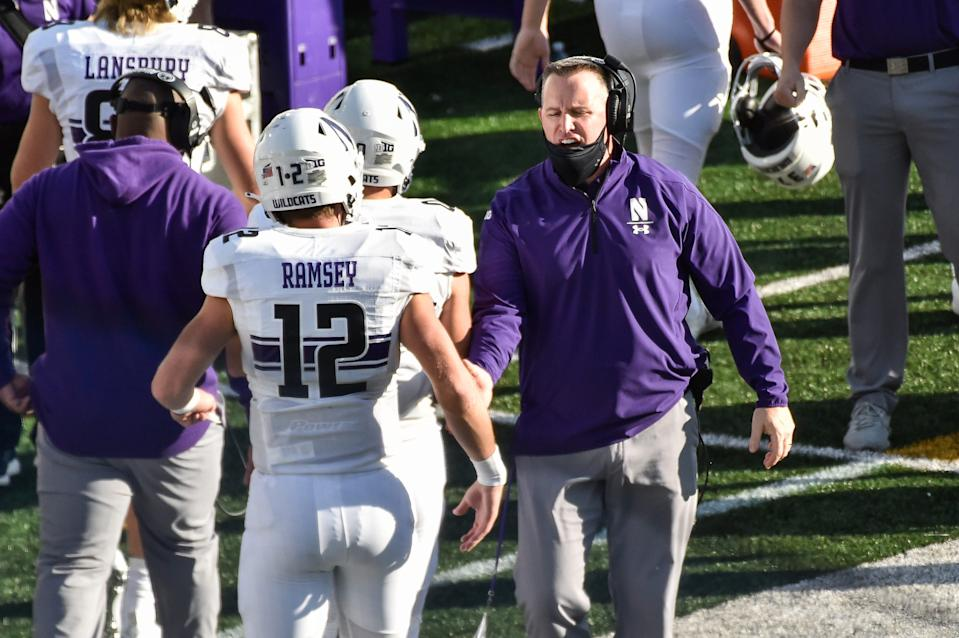 Oct 31, 2020; Iowa City, Iowa, USA; Northwestern Wildcats head coach Pat Fitzgerald celebrates with quarterback Peyton Ramsey (12) after a Wildcats touchdown against the Iowa Hawkeyes during the second quarter at Kinnick Stadium. Mandatory Credit: Jeffrey Becker-USA TODAY Sports