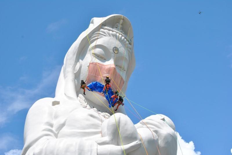 Workers place a mask on a 57-metre-high statue of Buddhist goddess Kannon to pray for the end of the coronavirus disease (COVID-19) pandemic at Houkokuji Aizu Betsuin temple in Aizuwakamatsu, Fukushima Prefecture, Japan