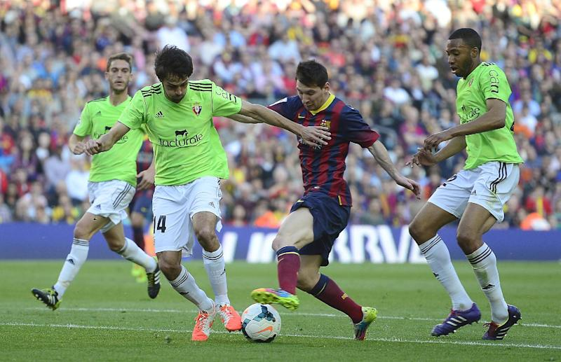 FC Barcelona's Lionel Messi, from Argentina, center, duels for the ball against Osasuna's Alejandro Arribas during a Spanish La Liga soccer match at the Camp Nou stadium in Barcelona, Spain, Sunday, March 16, 2014. (AP Photo/Manu Fernandez)