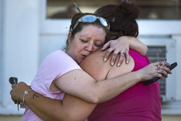 <p>Carrie Matula hugs a woman who lost her father in a mass shooting at the First Baptist Church in Sutherland Springs, Texas, Nov. 5, 2017. Matula said she saw and heard everything as it happened from the gas station where she works just a block away. (Nick Wagner / American-Statesman via AP) </p>