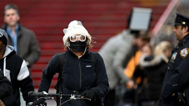 PHOTO: A woman wearing a mask pushes her bike in Times Square, on March 18, 2020 in New York City. (Johannes Eisele/AFP via Getty Images)