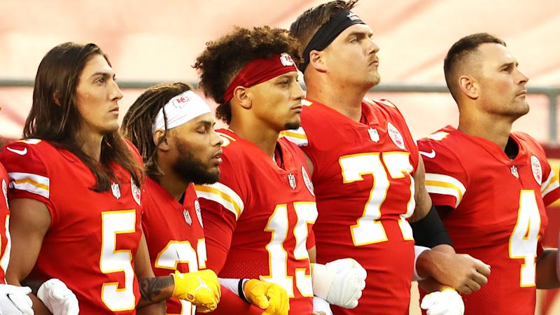 The Kansas City Chiefs are pictured with arms linked.