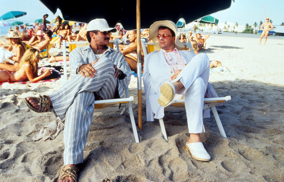 Robin Williams and Nathan Lane sitting under an umbrella on the sand at the beach in a scene from the film 'The Birdcage', 1996. (Photo by United Artists/Getty Images)