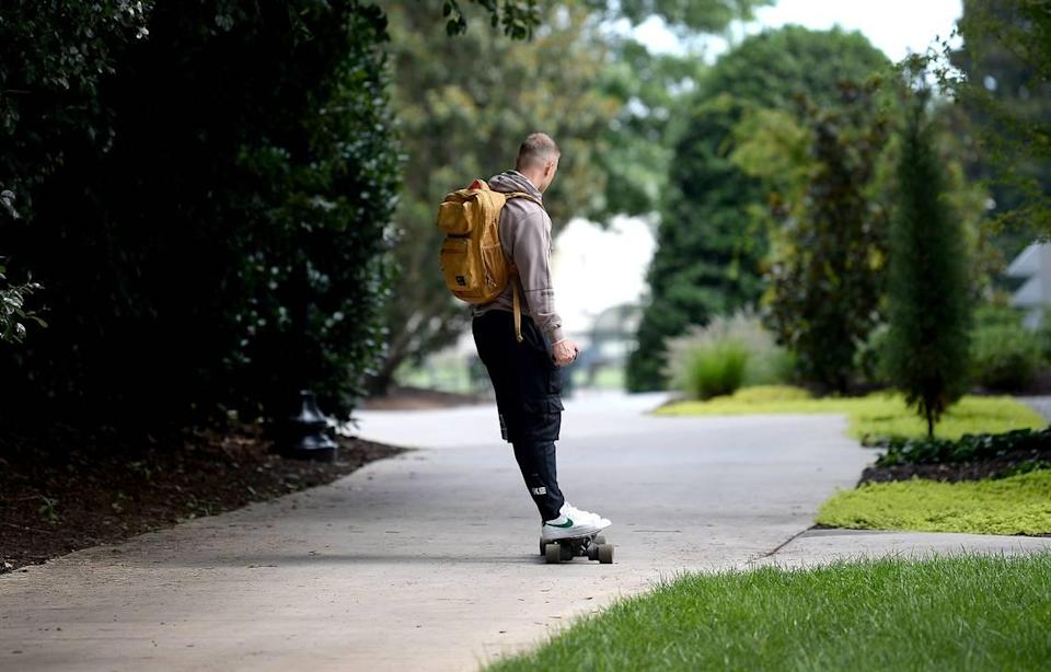 Carolina Panthers running back Christian McCaffrey rides a skateboard down a path at Wofford College in Spartanburg on Tuesday. McCaffrey missed 13 of 16 games in 2020 due to injury.