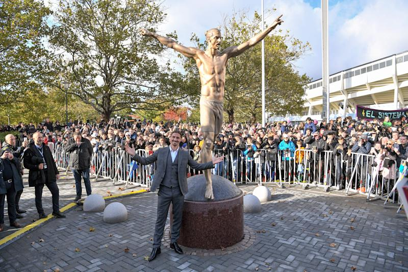 TOPSHOT - Sweden's biggest football star, Los Angeles Galaxy's forward Zlatan Ibrahimovic poses next to the 2,7 m bronze statue of him, after the unveiling ceremony on October 8, 2019 near the stadium where he made his professional debut in his hometown of Malmo in southern Sweden. (Photo by Johan NILSSON / TT News Agency / AFP) / Sweden OUT (Photo by JOHAN NILSSON/TT News Agency/AFP via Getty Images)