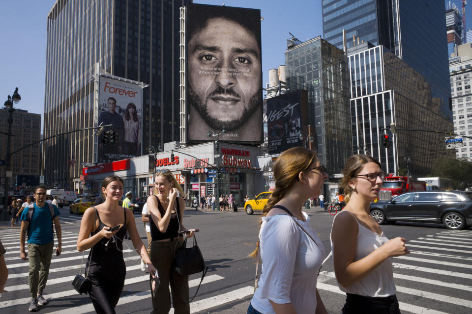 """FILE - In this Sept. 6, 2018 file photo, people walk by a Nike advertisement featuring Colin Kaepernick in New York. In his """"Just Do It"""" spot for Nike that marked the campaign's 30th anniversary in September, the sidelined-by-kneeling NFL quarterback somberly challenged viewers to """"believe in something, even if it means sacrificing everything."""" Some responded with anger, cutting or burning Nike gear and calling for boycotts. President Donald Trump slammed the company's move, while LeBron James defended it, saying he stands for those who believe in change. (AP Photo/Mark Lennihan, File)"""