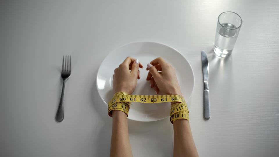 Hands tied with tapeline on empty plate, girl obsessed with counting calories