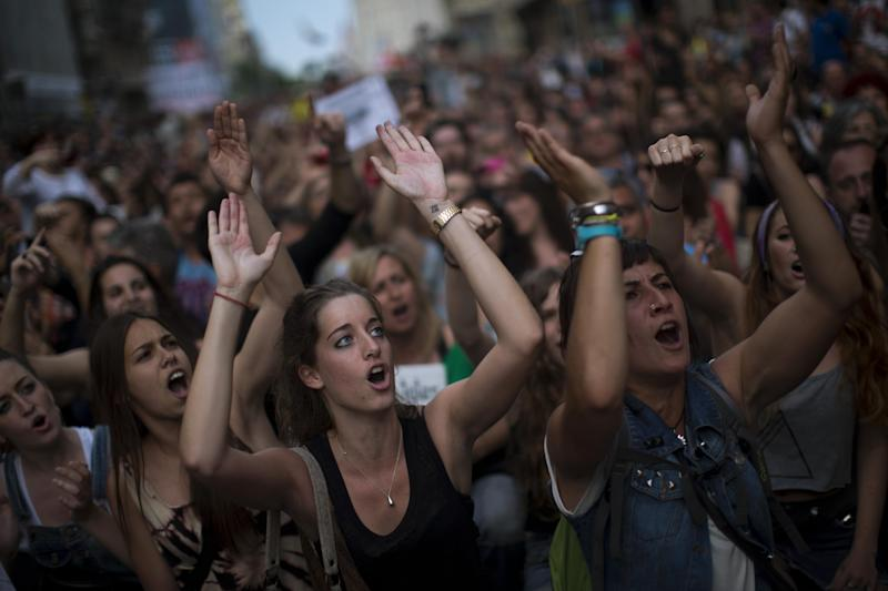 """Demonstrators shout slogans during a protest to mark the anniversary of the beginning of the """"Indignados"""" movement in Barcelona, Spain, Saturday May 12, 2012. Spanish activists angered by grim economic prospects planned nationwide demonstrations Saturday to mark the one-year anniversary of their protest movement that inspired similar groups in other countries. The protests began May 15 last year and drew hundreds of thousands of people calling themselves the Indignant Movement. The demonstrations spread across Spain and Europe as anti-austerity sentiment grew. (AP Photo/Emilio Morenatti)"""