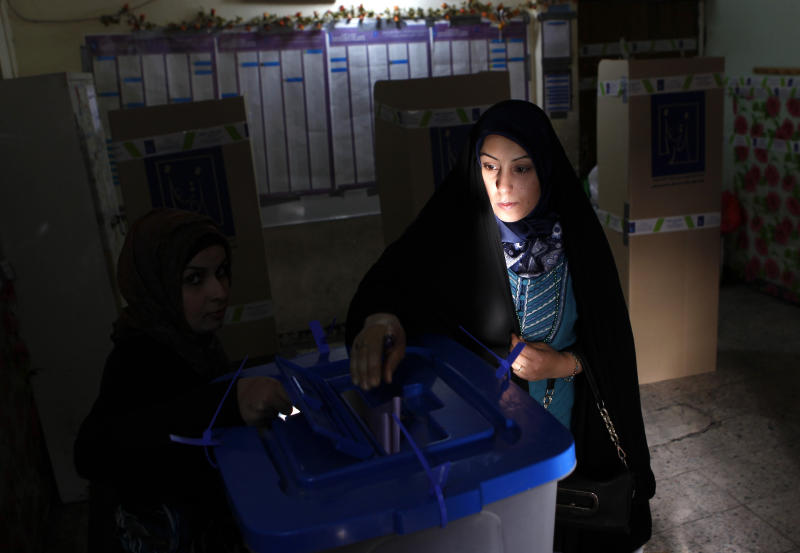 An Iraqi woman, the last voter in a polling center in the Karrada neighborhood, polling center casts her ballot just before polls closed in the country's provincial elections in Baghdad, Iraq, Saturday, April 20, 2013. Iraqis passed through security checkpoints and razor-wire cordons to vote in the country's first vote since the U.S. military withdrawal, marking an important test of the country's stability. (AP Photo/ Hadi Mizban)