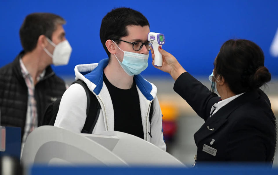 Passengers wearing face masks have their temperature taken at a British Airways check-in desk at Heathrow airport, west London July 10, 2020. — AFP pic