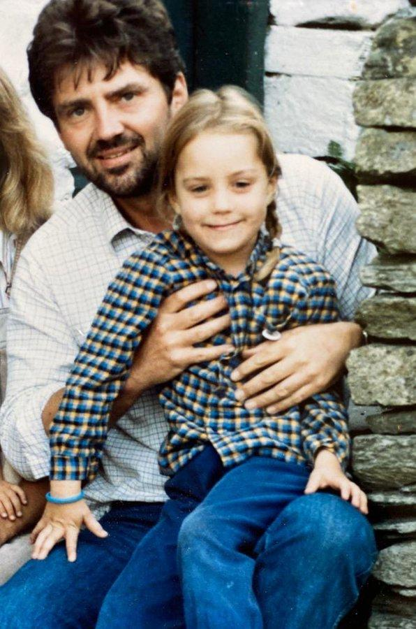 Kate as a child with her father, Michael Middleton. She looks ready to burst out from her father's lap so she can run around - hair out of the way in plaits, ready for fun. (Kensington Royal)
