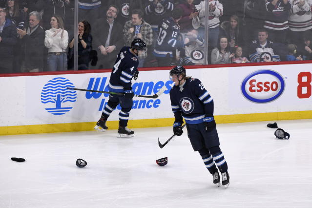 Winnipeg Jets' Patrik Laine (29) skates by hats thrown on the ice after scoring his third goal against the Ottawa Senators during third period NHL action in Winnipeg on Saturday Feb. 8, 2020. (Fred Greenslade/The Canadian Press via AP)