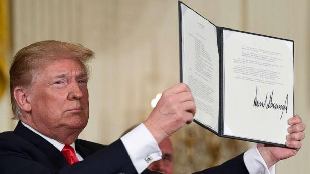 PHOTO: President Donald Trump holds up the space policy directive that he signed during a National Space Council meeting in Washington, June 18, 2018. (Susan Walsh/AP)