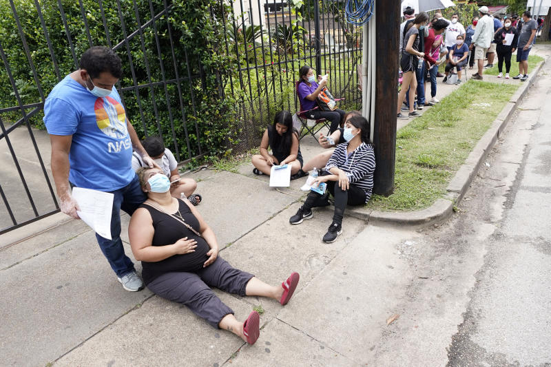 People wait in line at a free COVID-19 testing site provided by United Memorial Medical Center, Sunday, June 28, 2020, at the Mexican Consulate, in Houston. Confirmed cases of the coronavirus in Texas continue to surge. Texas Gov. Greg Abbott shut down bars again and scaled back restaurant dining on Friday as cases climbed to record levels after the state embarked on one of America's fastest reopenings. (AP Photo/David J. Phillip)