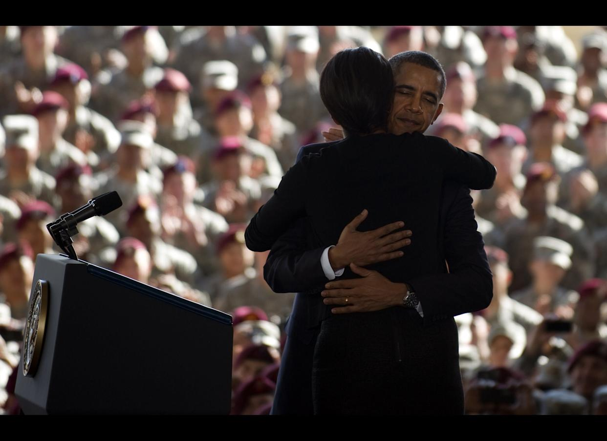 First Lady Michelle Obama (C) is hugged by US President Barack Obama as they deliver remarks to troops and military families at Fort Bragg, NC, December 14, 2011. Obama on Wednesday marked the US exit from Iraq by eulogizing fallen troops and seek to move Americans on from a divisive near nine-year war which he opposed. AFP PHOTO/Jim WATSON (Photo credit should read JIM WATSON/AFP/Getty Images)