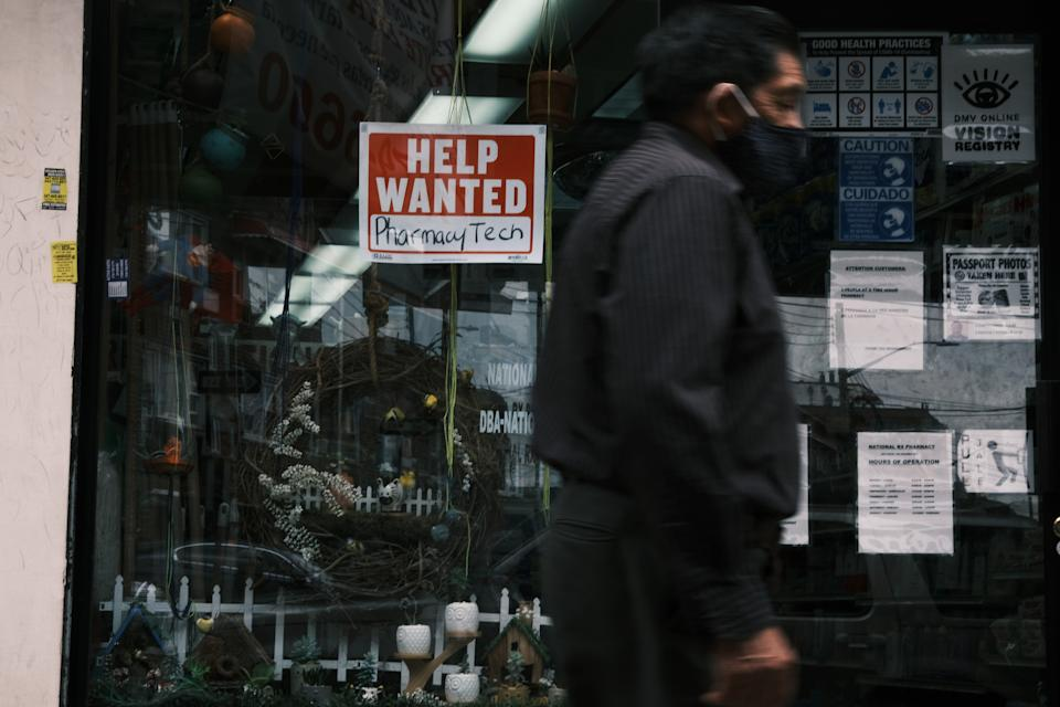 People walk by a Help Wanted sign in New York City on June 04, 2021 as the U.S. economy added 559,000 jobs in May, bringing the unemployment rate down to 5.8% from 6.1%. (Photo by Spencer Platt/Getty Images)