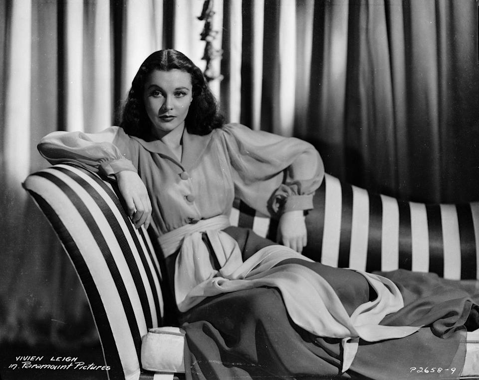 <p>Vivien Leigh leans back on a striped chaise, wearing a chiffon dress with bishop sleeves and a ribbon at the waist. </p>