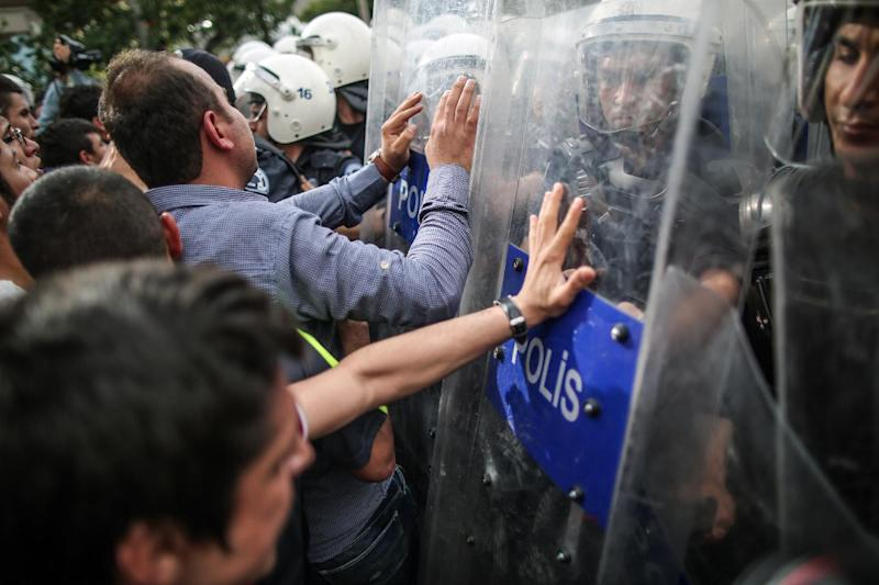 "Riot police try to stop protesters who were attacking the Soma offices of Prime Minister Recep Tayyip Erdogan's Justice and Development Party during his visit to the coal mine in Soma, Turkey, Wednesday, May 14, 2014. A violent protest erupted Wednesday in the Turkish city of Soma, where at least 238 coal miners have died after a mine explosion. Many in the crowd expressed anger at Prime Minister Recep Tayyip Erdogan's government. Rocks were being thrown and some people were shouting that Erdogan was a ""Murderer!"" and a ""Thief!"" (AP Photo/Emrah Gurel)"