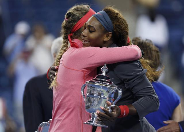 Serena Williams of the U.S. holds her winner's trophy as she embraces Victoria Azarenka of Belarus after Williams won their women's singles final match at the U.S. Open tennis championships in New York September 8, 2013. REUTERS/Adam Hunger (UNITED STATES - Tags: SPORT TENNIS)