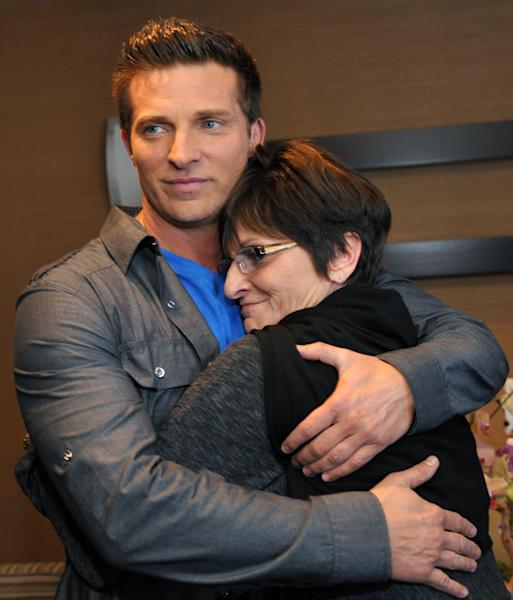 "This Feb. 27, 2013 file photo shows Jill Farren Phelps, right, executive producer of ""The Young and the Restless,"" huging cast member Steve Burton at the Hot New Faces of ""The Young and the Restless"" press junket in Los Angeles. CBS' soap ""The Young and the Restless"" has a leading 23 Daytime Emmy nominations, followed by its ABC rival ""General Hospital"" with 19. Nominations for the 40th annual Daytime Emmy awards were announced on Wednesday morning. The award ceremony will be held June 16 in Beverly Hills, Calif., televised for the second year on the cable network HLN. (Photo by Chris Pizzello/Invision/AP, file)"