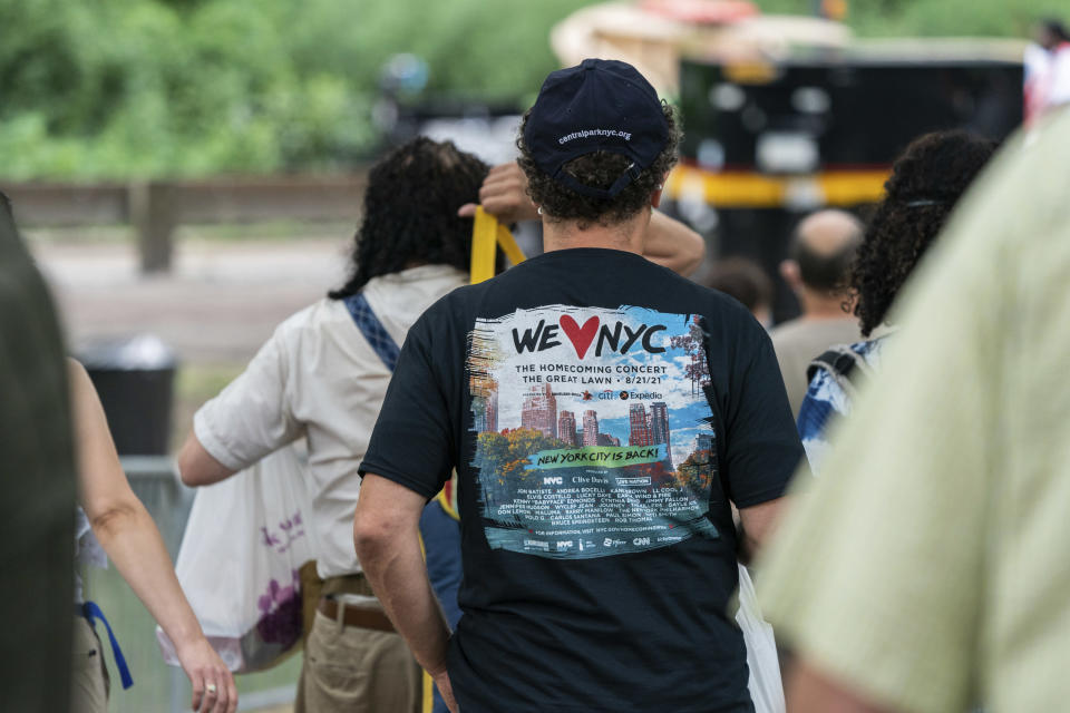 """A man wears a T-shirt reading """"WE love NYC"""" before the """"We Love NYC: The Homecoming Concert"""" in New York's Central Park, Saturday, Aug. 21, 2021. We Love NYC, The Homecoming Concert celebrate its recovery from the coronavirus pandemic despite surging cases and hospitalizations due to the delta variant. (AP Photo/Jeenah Moon)"""