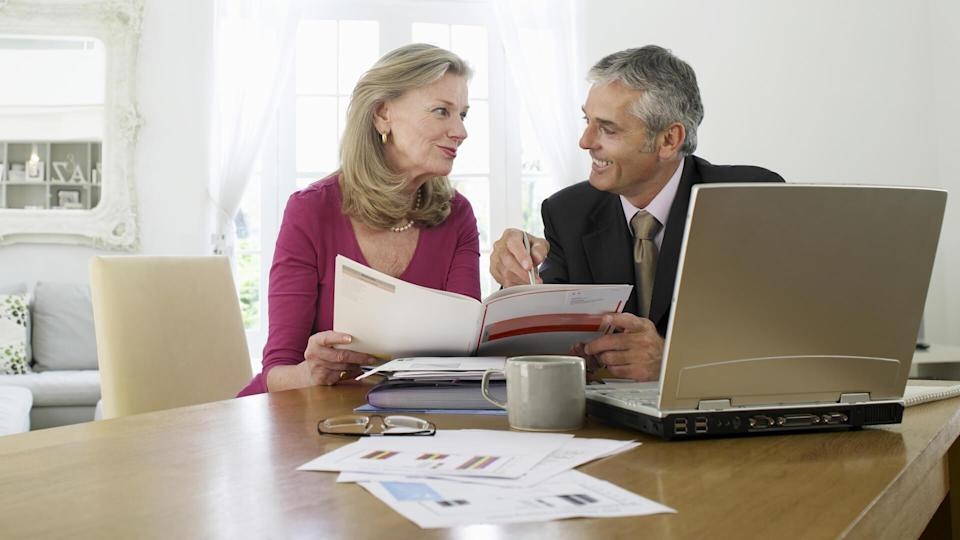 Mature woman sitting at table with financial advisor.